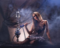 A young woman smoking a hookah sexy in luxury underwear the image is taken on vintage interior Royalty Free Stock Photo