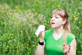 Young woman sneezing in a flowers meadow concept seasonal allergy Stock Image
