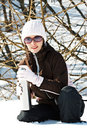 Young woman in snow with thermos bottle Stock Images