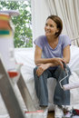 Young woman on sofa with paint roller, paint pot on ladder in foreground (differential focus) Royalty Free Stock Photo