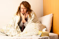 Young woman with sore throat in bed covered blanket Stock Photos
