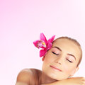 Young woman at spa salon beautiful girl sleeping on massage table pretty female with pink orchid in her hair attractive lady Stock Photography