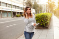 Young woman speaking on mobile phone while walking city avenue and holding a coffee cup Royalty Free Stock Images