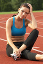 Young Woman in Sports Bra Resting on Track Royalty Free Stock Images