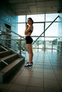 Young woman in sports clothes athletic build modern interior with stages Royalty Free Stock Image