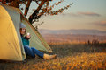 Young woman in sports wear and trekking shoes sitting in bivouac beautiful colorful light olive with metal mug hands at autumn Stock Photos