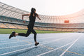 Young woman in sportswear sprinting on running track stadium at sunset Royalty Free Stock Photo