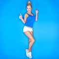Young woman squinting showing thumb up sign blue background Royalty Free Stock Photo