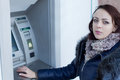 Young woman standing at an atm machine outside a bank waiting to withdraw money from automated teller Royalty Free Stock Photo