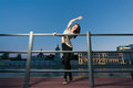 A young woman is standing in a ballet position using as barre the railing on the waterfront Royalty Free Stock Image
