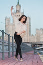 A young woman is standing in a ballet position on the waterfront background of high building Stock Image