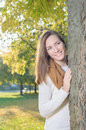 Young woman standing behind tree outdoor in park girl Royalty Free Stock Image