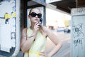 Young woman standing chatting on a public phone beautiful in sunglasses pay in booth at the side of an urban street Royalty Free Stock Photos