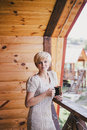 Young woman standing on the cozy balcony with a cup of tea pretty hot or coffee or cocoa Royalty Free Stock Photo
