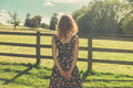 Young woman standing in field by fence on summer day Royalty Free Stock Photo