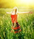 Young woman is standing in meadow enjoying sunlight Royalty Free Stock Photo