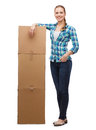 Young woman standing next to tower of boxes happiness postal and people concept smiling Royalty Free Stock Photography