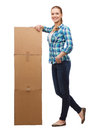 Young woman standing next to tower of boxes happiness postal and people concept smiling Stock Photos