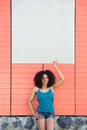Young woman standing outdoors portrait of a and pointing finger to blank poster Royalty Free Stock Photos