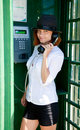 Young woman is standing at phonebox Royalty Free Stock Images
