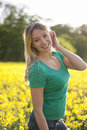 A young woman standing in a seed field smiling Royalty Free Stock Photo
