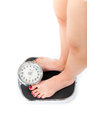 Young woman standing on a scale diet and weight only feet to be seen Stock Image