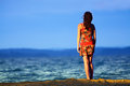 Young woman standing on seacoast on sunset Royalty Free Stock Photo