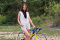 Young woman stands with a bicycle on a forest road Royalty Free Stock Photo