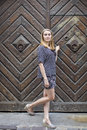 Young woman stands in front of an ancient door. Travel. Royalty Free Stock Photo