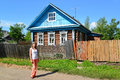 The young woman stands near the rural wooden house Royalty Free Stock Photo