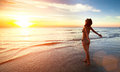 Young woman stands towards the sun on Sea beach during a amazing sunset. Royalty Free Stock Photo