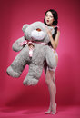 Young woman in stockings erotic stroking her favorite soft toy female over pink with posing Royalty Free Stock Photos
