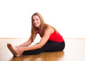 Young woman stretching exercising and in the studio on a hardwood floor sitting on the floor reaching down to hold her toes Stock Images