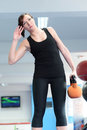 Young woman stretching with kettle bell weight working out weights personal trainer in gym Stock Image