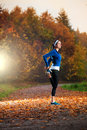 Young woman stretching before running in the early evening in th autumn Royalty Free Stock Photography