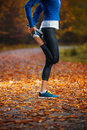 Young woman stretching before running in the early evening in th autumn Stock Images