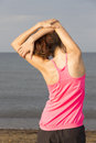 Young woman stretching triceps on the beach Photos stock