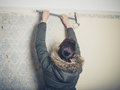 Young woman stripping wallpaper Royalty Free Stock Photo