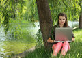 Young woman studying outside preety in a park under a willow tree near a pond Royalty Free Stock Photos