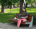 Young woman studying in a park sitting on bench and working on laptop Stock Image