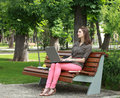 Young woman studying in a park sitting on bench and working on laptop Stock Images