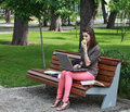 Young woman studying in a park sitting on bench and working on laptop while eating green apple Royalty Free Stock Photo