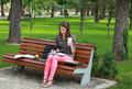 Young woman studying in a park sitting on bench and writing something notebook while holding disposable cup of coffee Royalty Free Stock Images