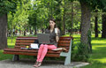 Young woman studying in a park working on laptop outside Royalty Free Stock Images