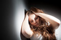 Young woman suffering from a severe depression anxiety very harsh lighting is used on this shot to underline the gloomy mood of Stock Images