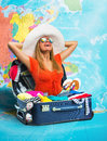 Young woman in suitcase on map cheerful full of clothing Stock Photography