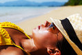 Young woman sun bathing on a sandy beach of thailand in yellow swimsuit hat and sunglasses laying down sunny summer day Stock Image