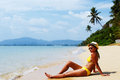 Young woman sun bathing on a sandy beach of thailand in yellow swimsuit hat and sunglasses seating down and sunny summer Royalty Free Stock Photo