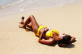 Young woman sun bathing on a sandy beach of thailand in yellow swimsuit and sunglasses laying down sunny summer day Stock Photos