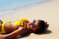 Young woman sun bathing on a sandy beach of thailand in yellow swimsuit and sunglasses laying down sunny summer day Royalty Free Stock Photos